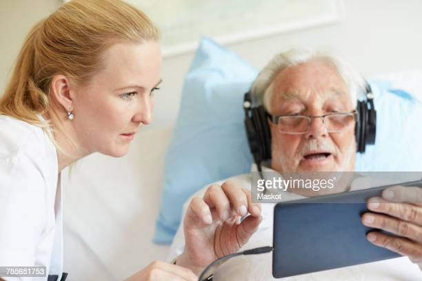 Female nurse assisting senior man in using digital tablet on hospital bed