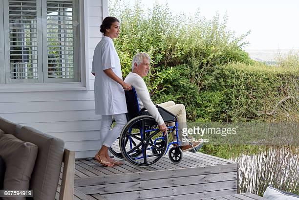 Female nurse assisting senior man in wheelchair on porch