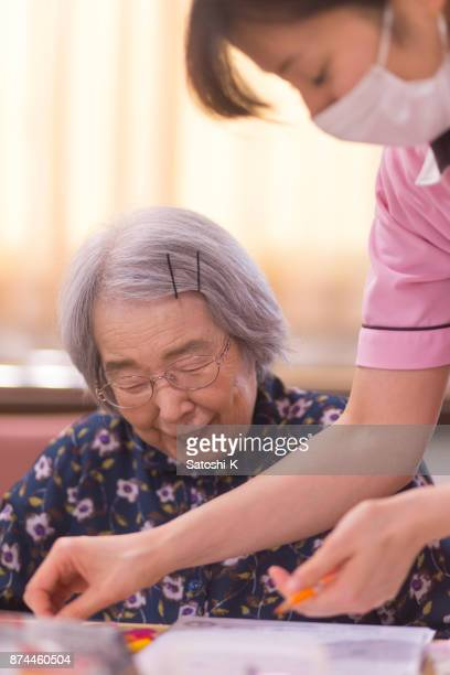 Female nurse assisting senior woman for drawing