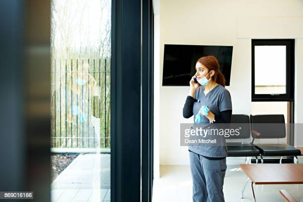 Female nurse at dental clinic talking on mobile phone