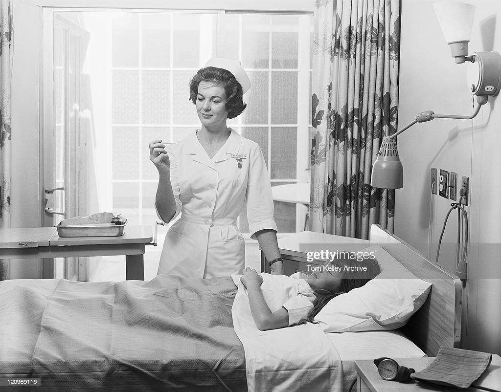 Female nurse checking girl's temperature : Stock Photo