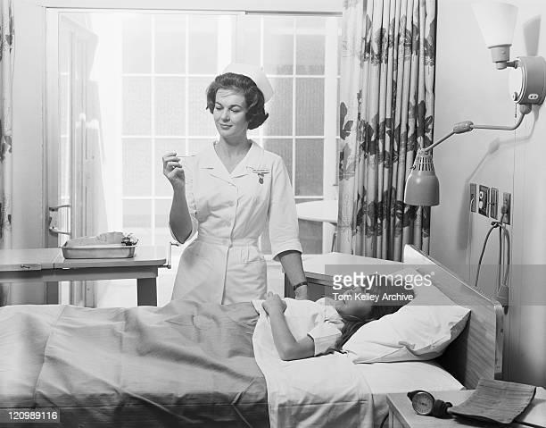 weibliche krankenschwester, die mädchen-temperatur - archivmaterial stock-fotos und bilder