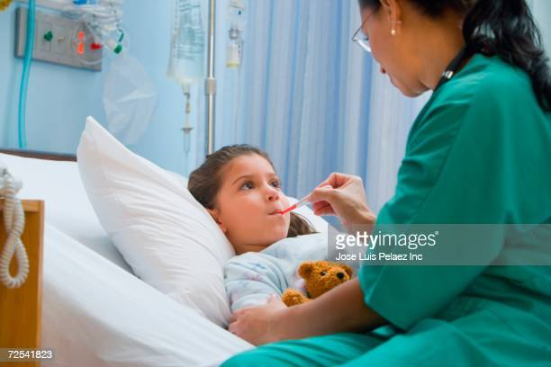 female nurse checking girl's temperature - girl in hospital bed sick stock photos and pictures