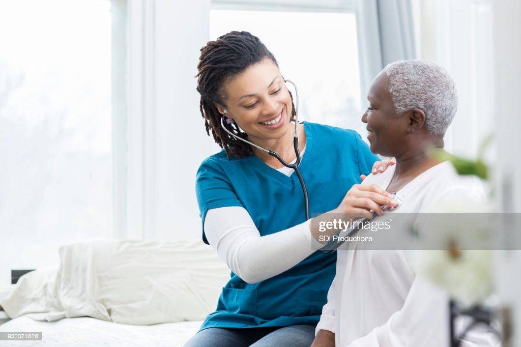 Female nurse checks patient's vital signs : Stock Photo