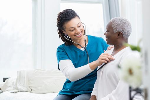 Female nurse checks patient's vital signs 932074828