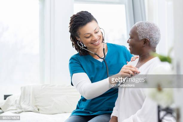female nurse checks patient's vital signs - visita imagens e fotografias de stock