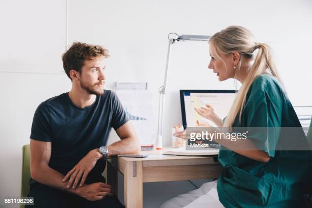 female nurse explaining to young male patient at office in hospital - male doctor stock photos and pictures