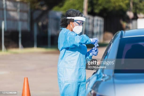女性看護師は患者にcovid検査を与える - ドライブスルー検査 ストックフォトと画像