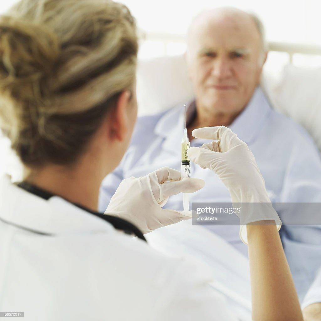 female nurse giving a senior man an injection : Stock Photo