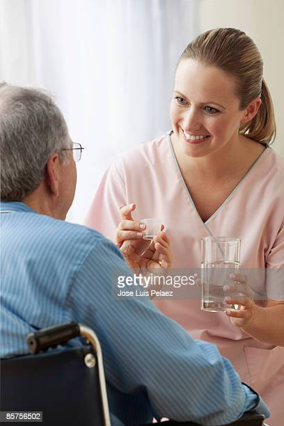 Female nurse giving male patient medication