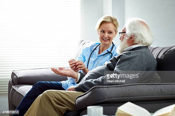 Female nurse giving medicine to elderly patient