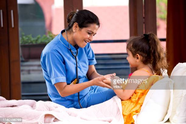 female nurse having fun with girl lying on bed during medical house call - medical insurance stock pictures, royalty-free photos & images