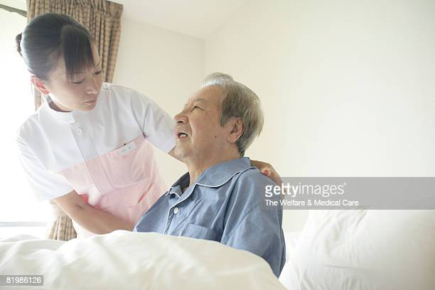 Female nurse helping mature man sit up on bed