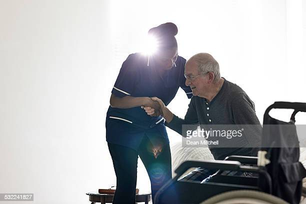 female nurse helping senior man get up from bed - nursing assistant stock pictures, royalty-free photos & images
