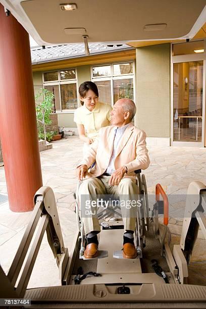 Female nurse helping senior man in wheelchair getting out of car