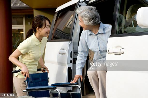 Female nurse helping senior woman getting out of car, smiling