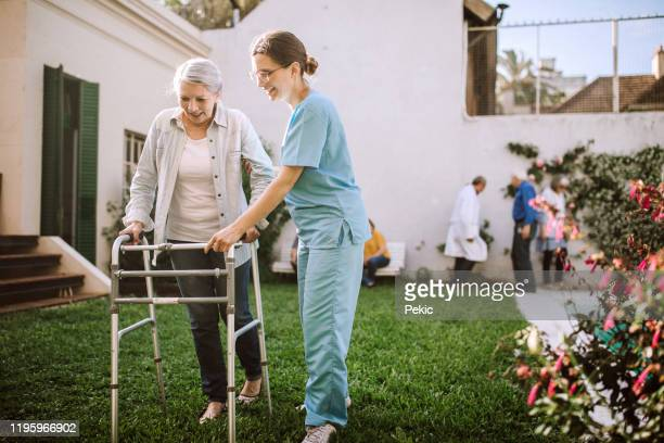 female nurse helping senior woman with mobility walker at nursing home - nursing assistant stock pictures, royalty-free photos & images