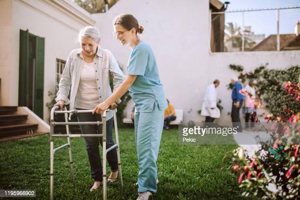 krankenschwester hilft seniorin mit mobilitäts-wanderer in pflegeheim - arzthelferin stock-fotos und bilder