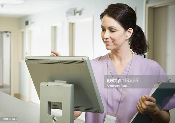 Female nurse holding clipboard, using computer at nurse's station