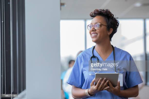 female nurse holding digital tablet smiles while looking out window - administrator stock pictures, royalty-free photos & images