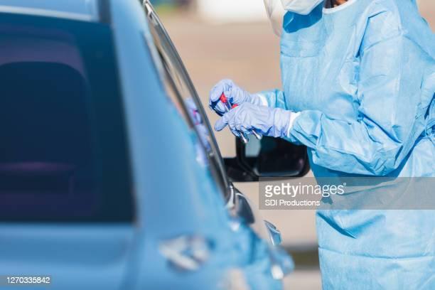 女性看護師はcovid-19テストキットを保持しています - ドライブスルー検査 ストックフォトと画像