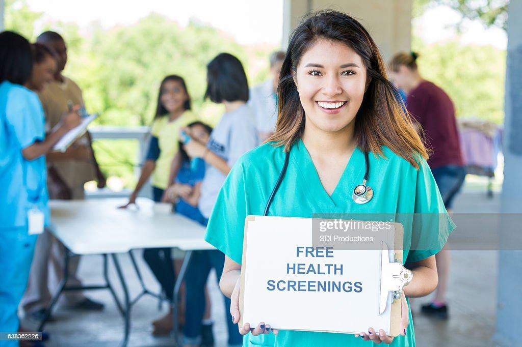 Female nurse holds 'Free Health Screenings' sign at health fair : Stock Photo
