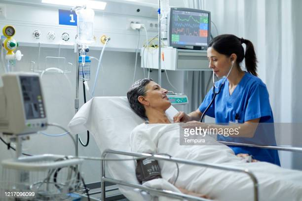 a female nurse is listening with a stethoscope the heart bit of a patient. - hospital ward stock pictures, royalty-free photos & images