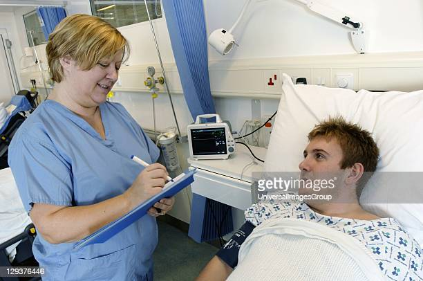 Female nurse is taking blood pressure of young male patient lying in hospital bed portable monitoring machine nearby