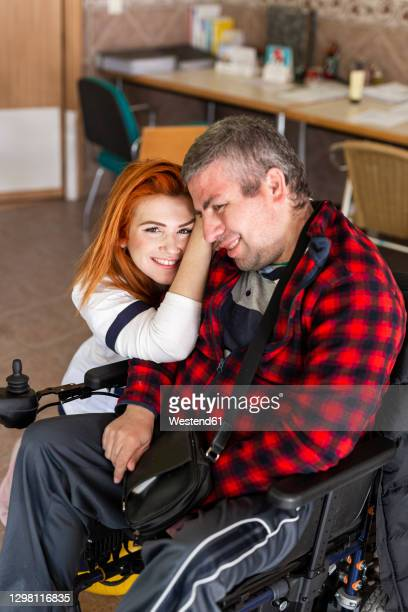 female nurse leaning on disabled man at nursing home - leaning disability stock pictures, royalty-free photos & images