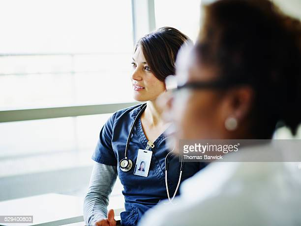 Female nurse listening during medical team meeting