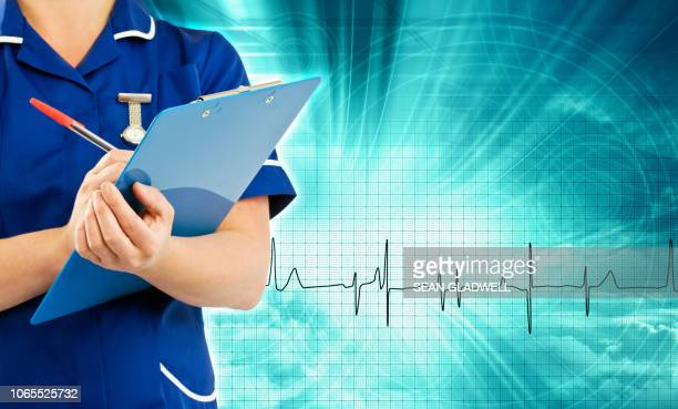 female nurse making notes - nhs staff stock pictures, royalty-free photos & images