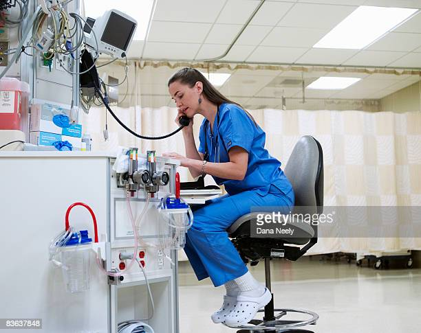 female nurse on phone in pacu of hospital  - healthcare stock pictures, royalty-free photos & images
