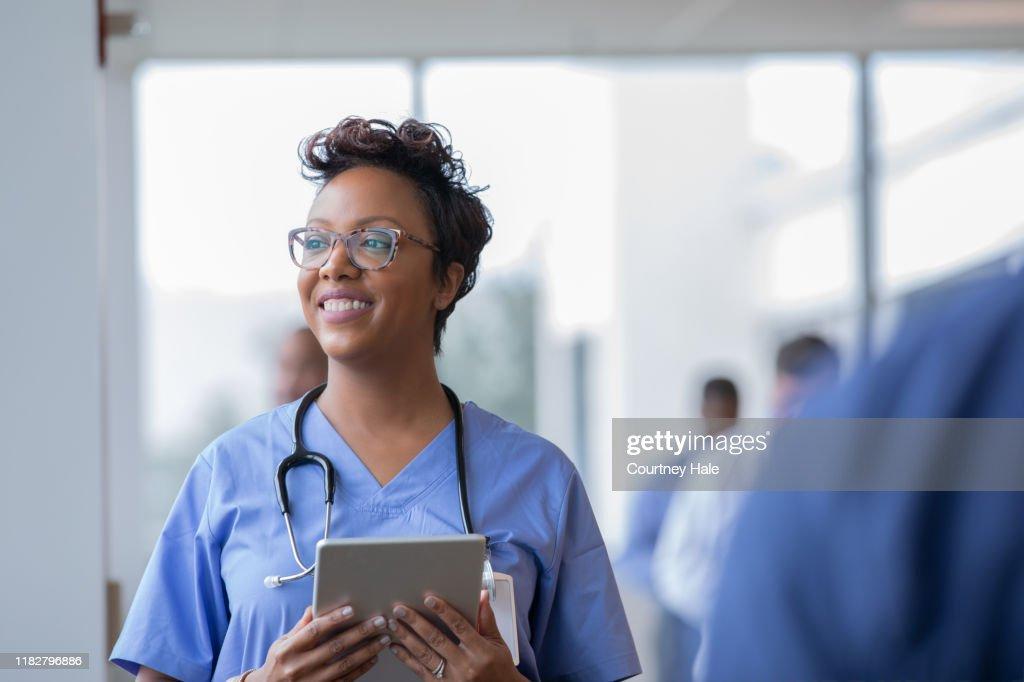 Vrouwelijke verpleegkundige of Arts glimlacht terwijl staren uit venster in ziekenhuis hal en het houden van digitale tablet met elektronische patiëntendossier : Stockfoto