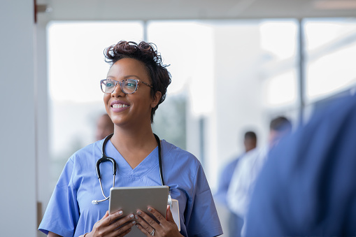 Female nurse or doctor smiles while staring out window in hospital hallway and holding digital tablet with electronic patient file 1182796886