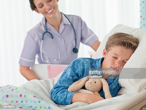 Female nurse overlooking a little boy (10-11) sleeping at hospital bed