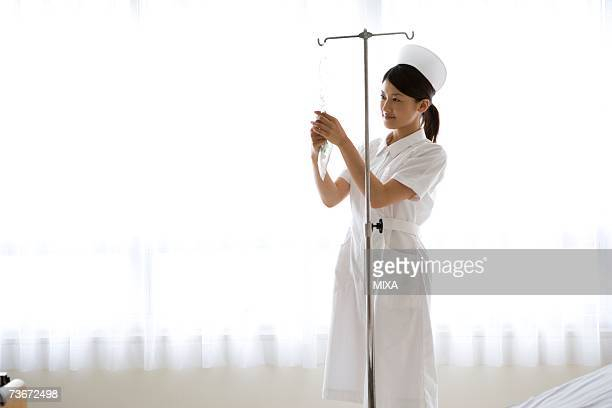 Female nurse preparing intravenous drip