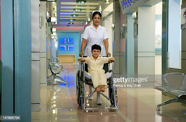 Female nurse pushing the wheelchair of a boy patient