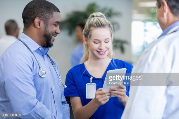 female nurse reading medical records on digital tablet to doctors in hospital corridor - civilian stock pictures, royalty-free photos & images