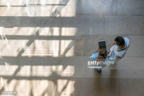 vrouwelijke verpleegster die iets aan arts op tablet in het ziekenhuis toont - ziekenhuis stockfoto's en -beelden