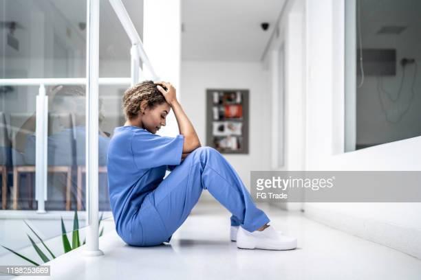 vrouwelijke verpleegsterzitting op de vloer en die radeloos kijkt - overwerkt stockfoto's en -beelden