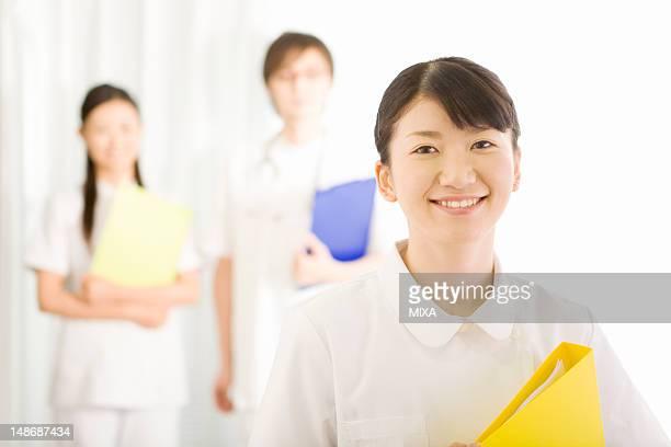 Female nurse smiling and holding file