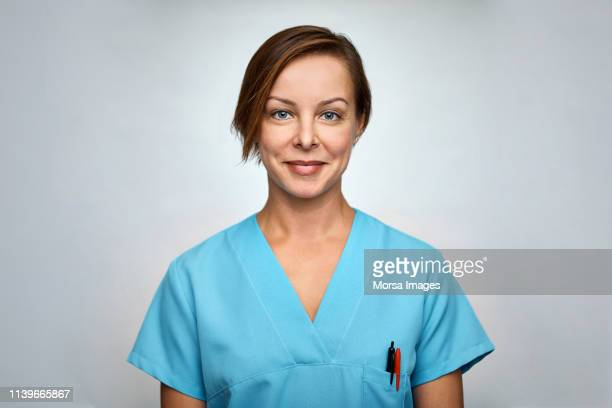 female nurse smiling over white background - 看護師 ストックフォトと画像