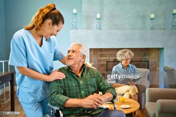 enfermeira fêmea que está pelo homem idoso deficiente - izusek - fotografias e filmes do acervo