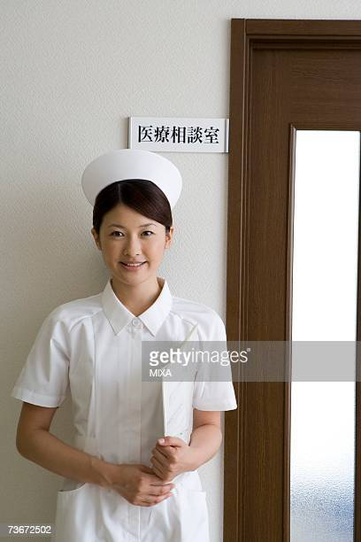 Female nurse standing in front of door