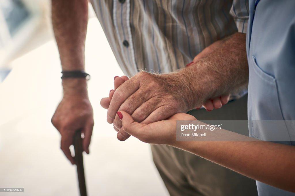 Female nurse supporting senior man to walk : Stock Photo