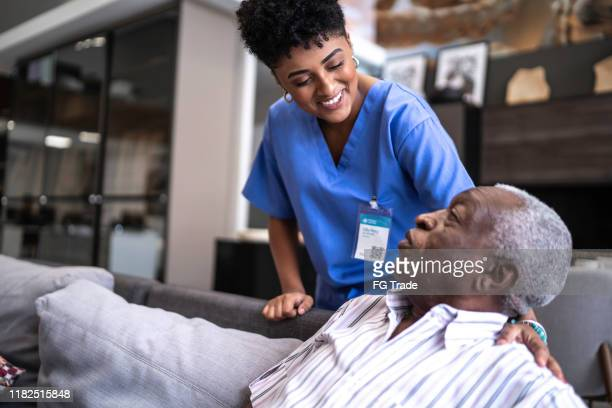 female nurse taking care of a senior man at home - community outreach stock pictures, royalty-free photos & images