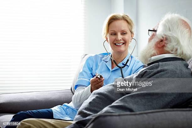 Weibliche Krankenschwester kümmert sich senior Mann wie zu Hause fühlen.