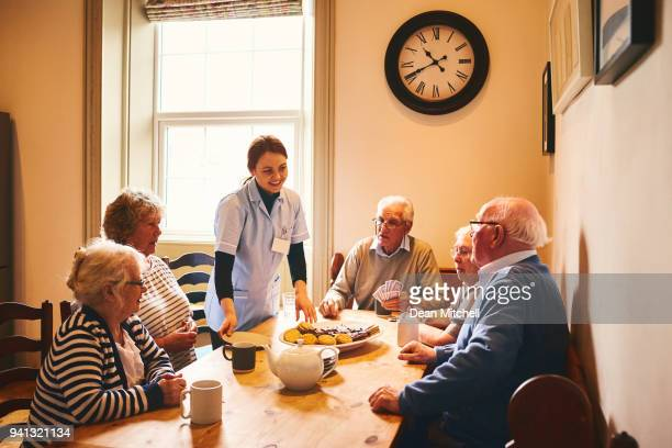 Female nurse taking care to seniors at retirement home