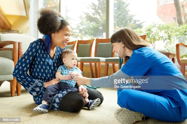 Female nurse talking to mother and baby in hospital waiting room