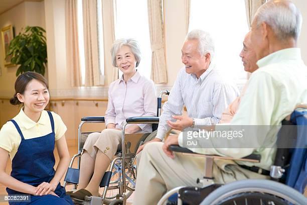 Female nurse talking to senior people sitting on wheelchair, smiling